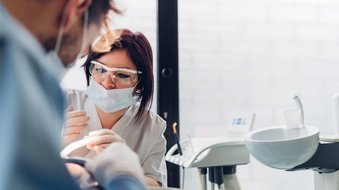 A dentist preparing to work on a patient who has signs of a tooth cavity.