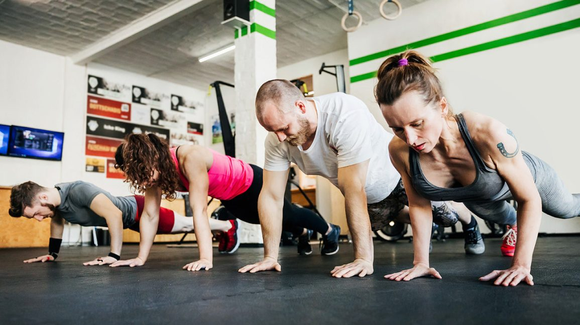 two men and two women doing pushups in a gym