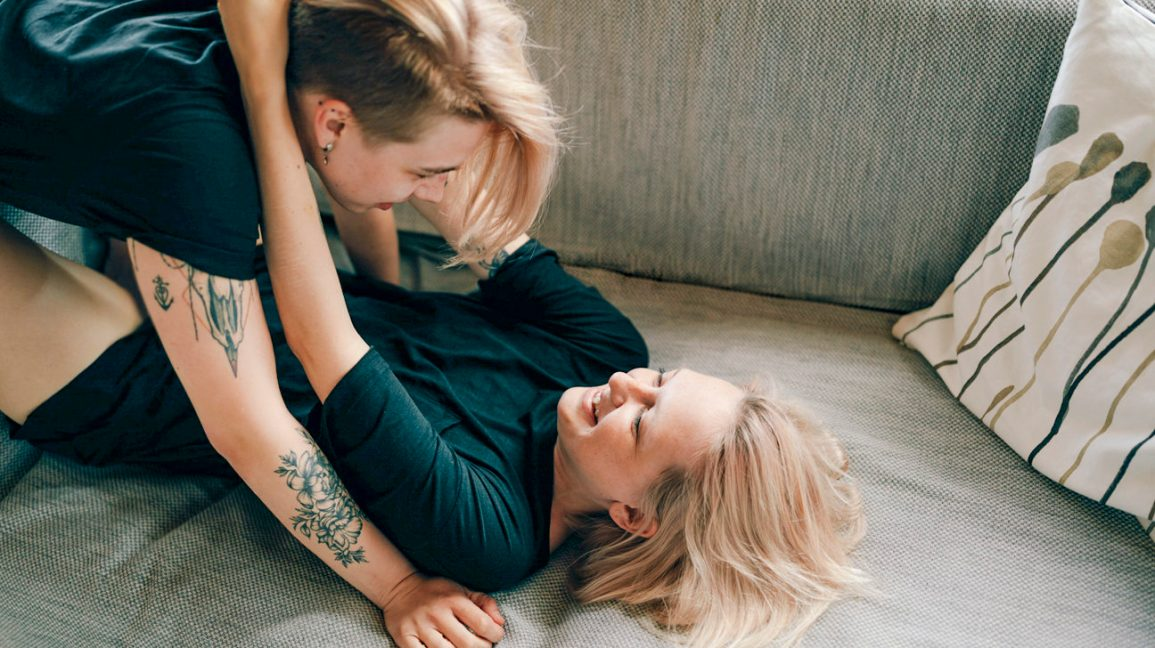 queer couple with their arms wrapped around each other, one person in a straddle position and the other laying on their back