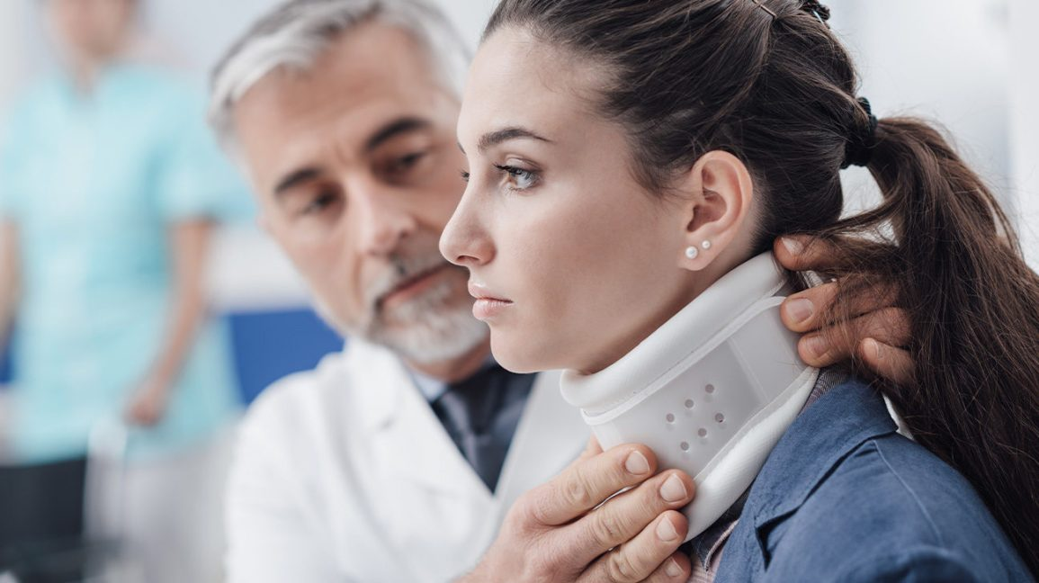 A doctor placing a cervical collar around a patient's neck.