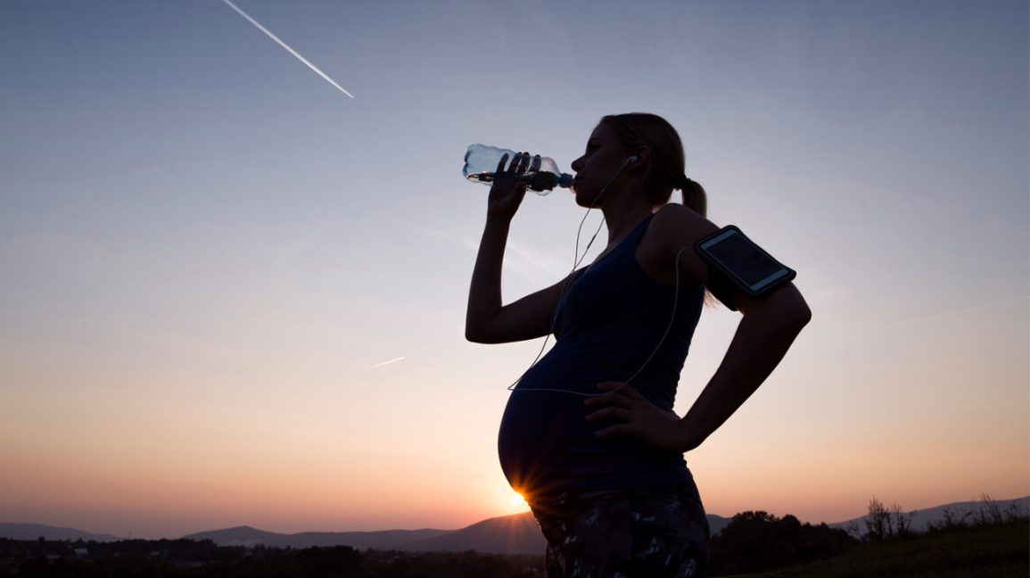 woman running while pregnant stops to drink water