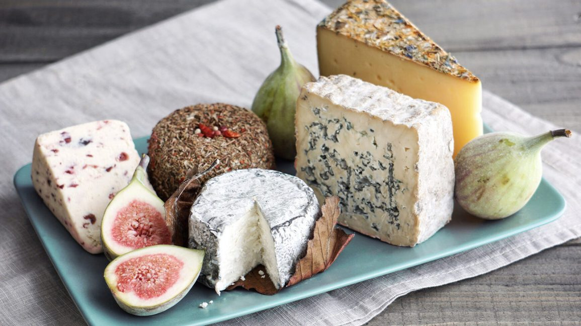 a platter of various types of cheese with figs