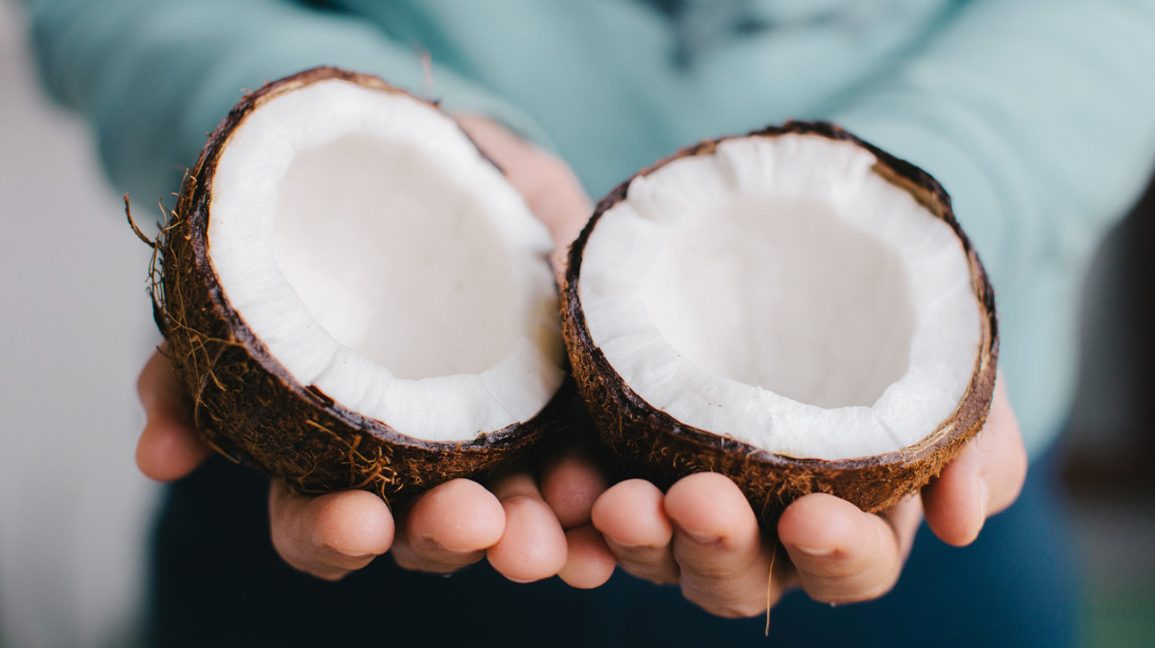 A person holding two coconut halves