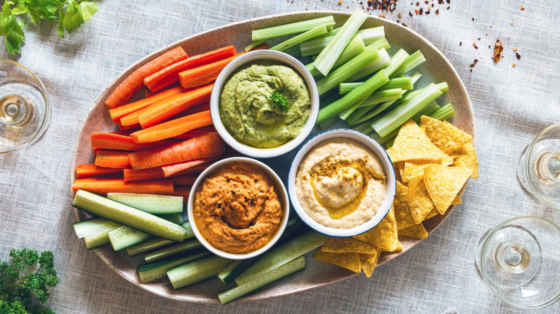 various hummus dips on a platter with raw veggies