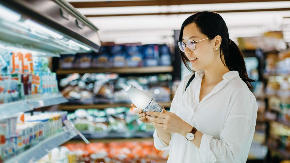 woman examining milk in grocery store