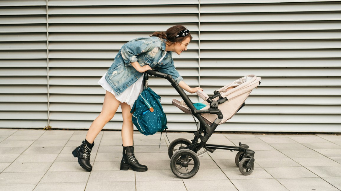 mom with diaper bag pushes baby in stroller