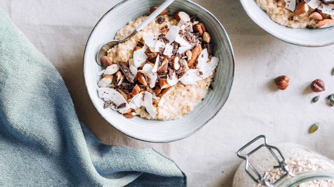 bowls of oatmeal with coconut, chocolate, and almonds