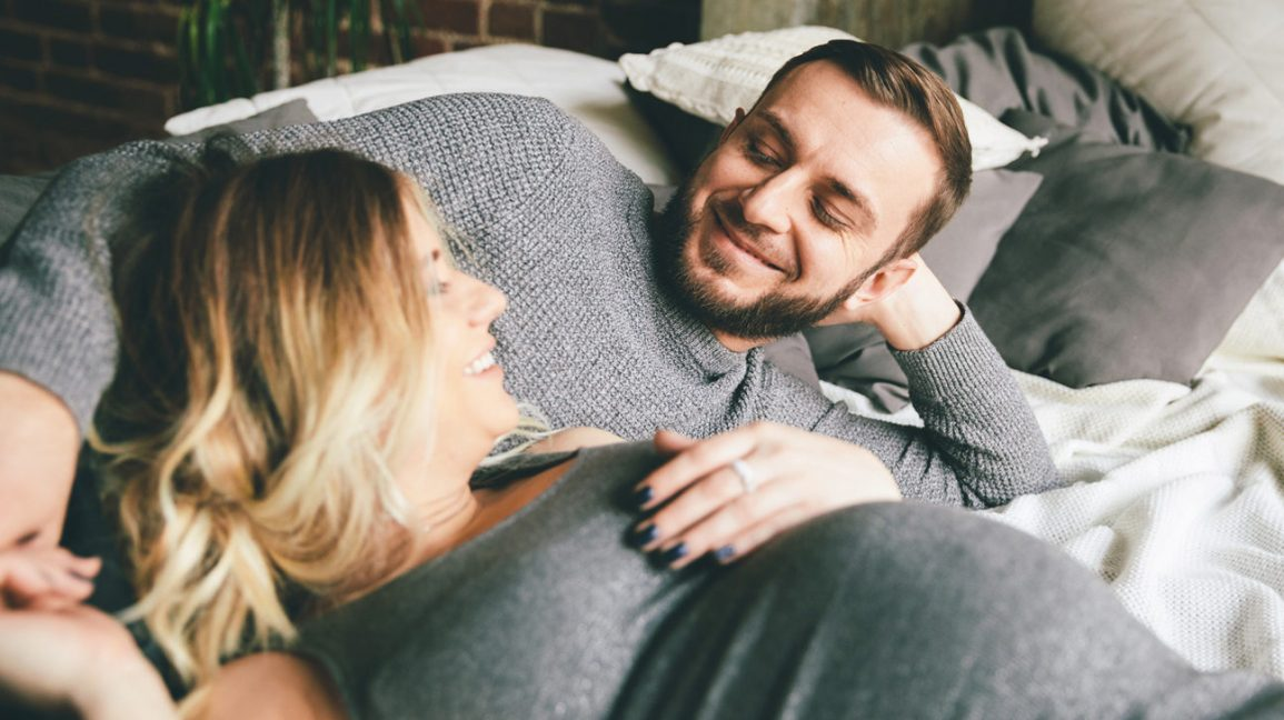 pregnant woman and man smiling in bed together