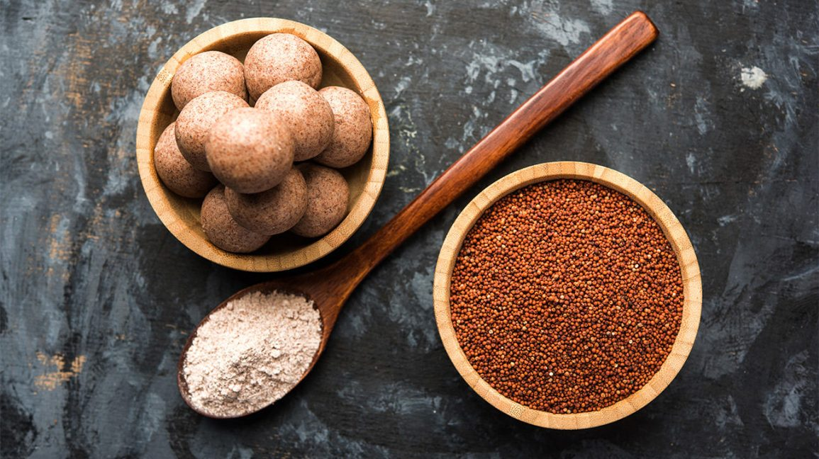 A bowl of ragi grain, a spoon with milled ragi, and a bowl with ragi dough balls
