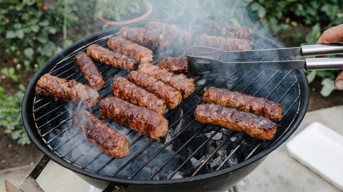 large sausages cooking on a grill