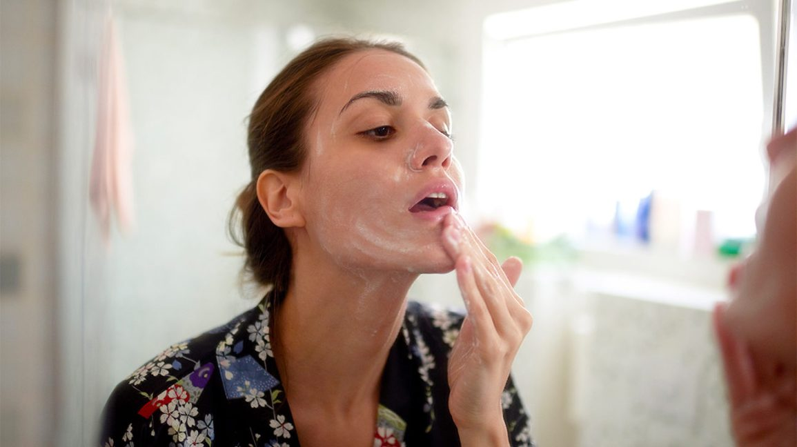 person applying a foaming cleanser to their face as part of their double cleansing routine