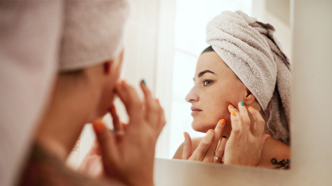 person with hair wrapped in a white towel looking in the bathroom mirror, gently pressing around a blemish on their jawline