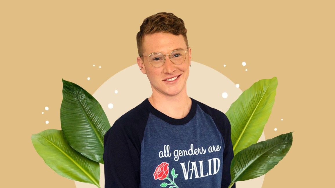 "Portrait of Mere Abrams against a beige mixed media background. Mere is wearing a navy blue raglan shirt that says ""all genders are valid"" on the front."