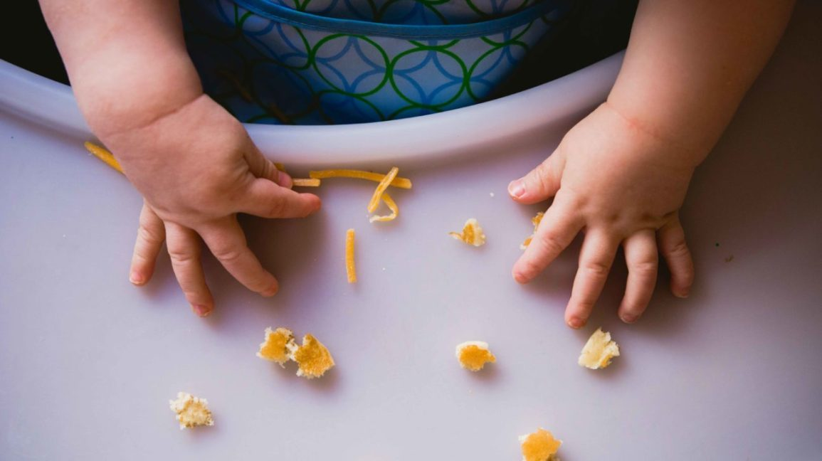 Closeup of toddler hands on high chair tray with food