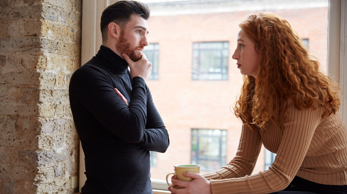 couple arguing in front of window