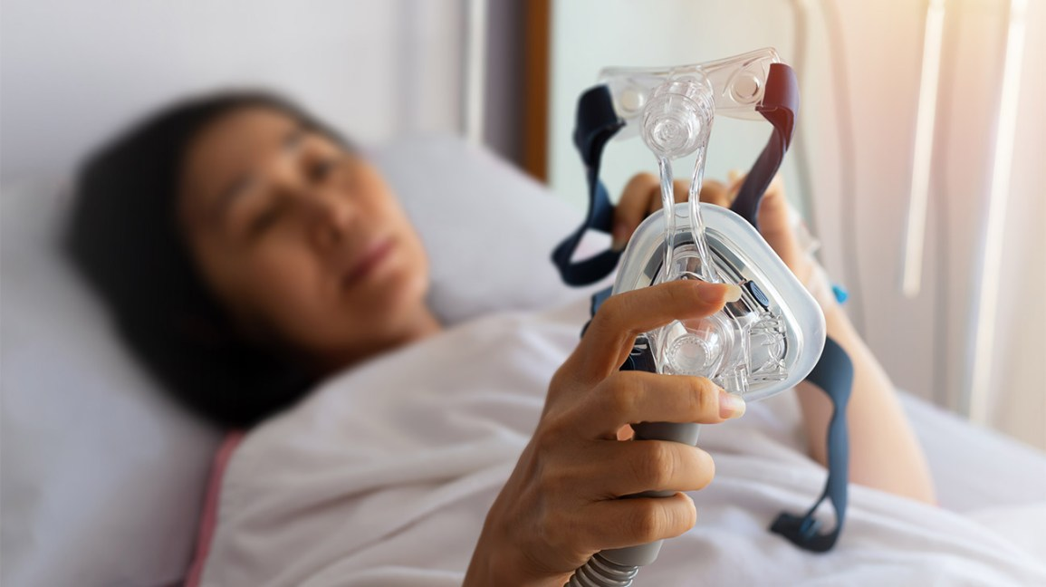 apap vs cpap, woman in bed with a CPAP mask