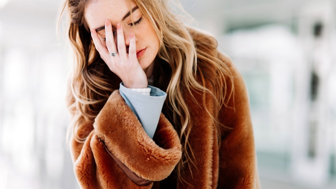 hungover woman in brown fuzzy coat holding hand to face