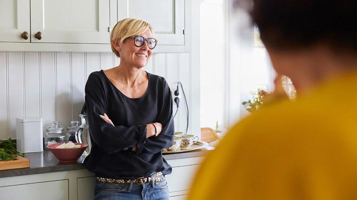 donna appoggiata al bancone della cucina
