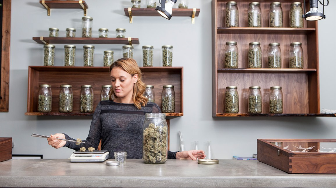 woman weighing weed from glass jars on a counter