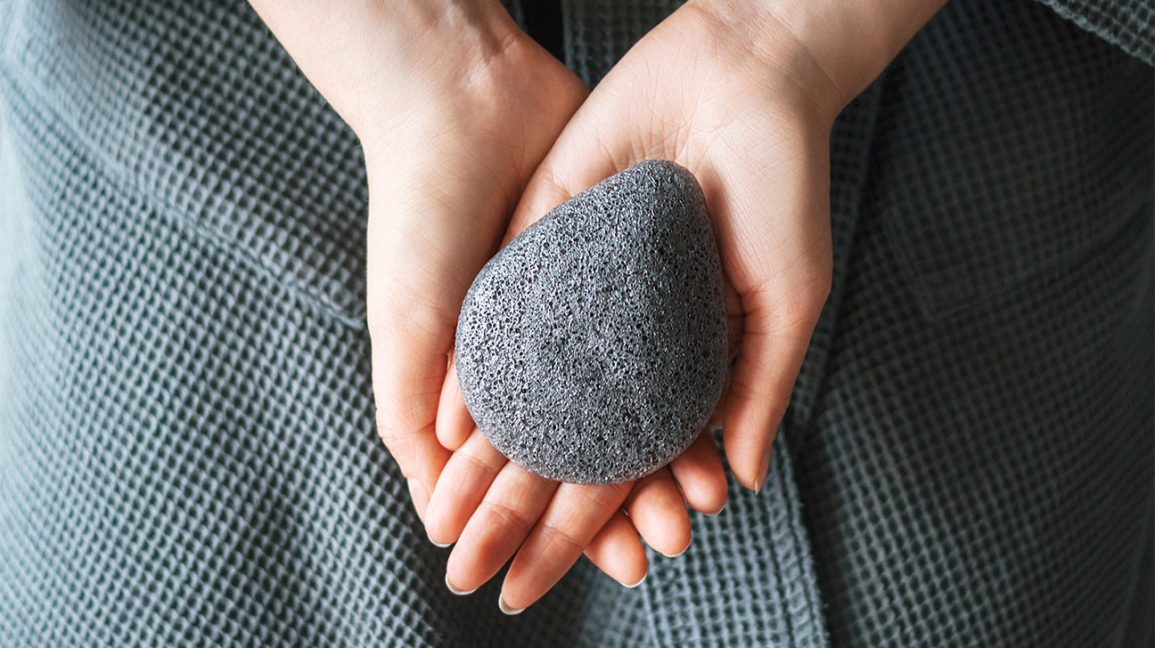 Hands holding a charcoal-infused konjac sponge.