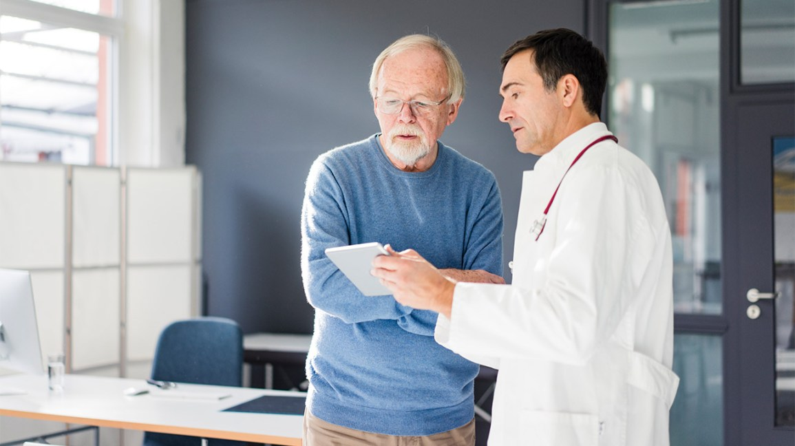 male doctor showing screen to male patient