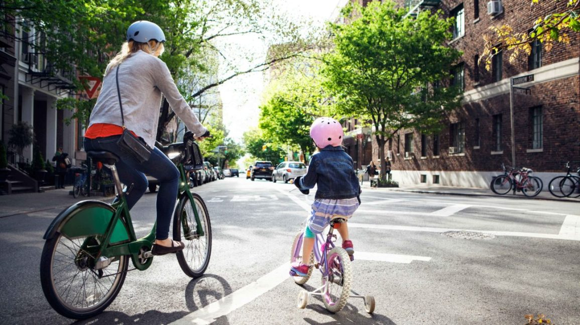 single mother and child ride bikes in the city