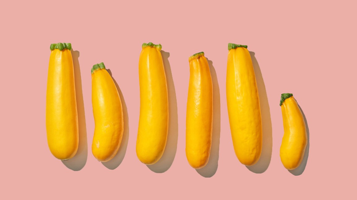 six yellow squash of varying length and girth in a horizontal row, set against a light pink background