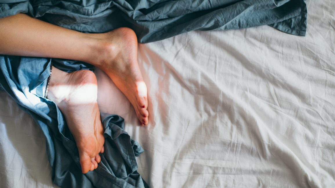 A person lying on a bed with their heels exposed.