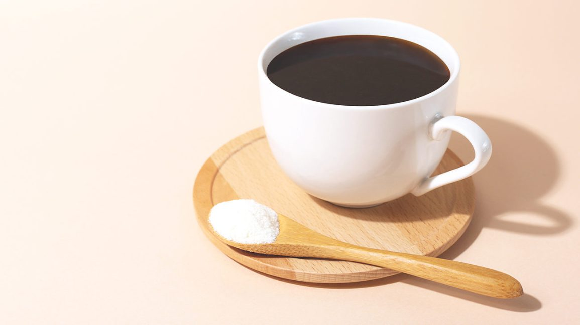 A cup of coffee and a spoon with collagen powder