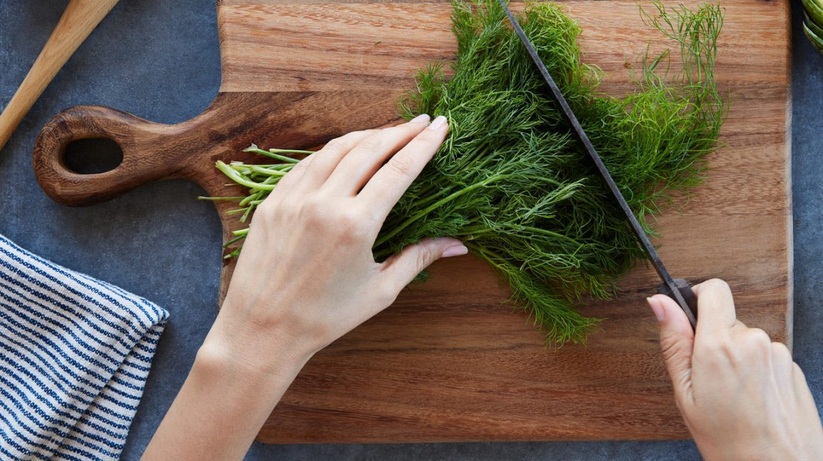 A person cutting fresh dill
