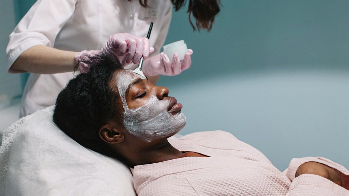 person wearing a robe, laying in a spa chair while an esthetician applies a mud mask to their face