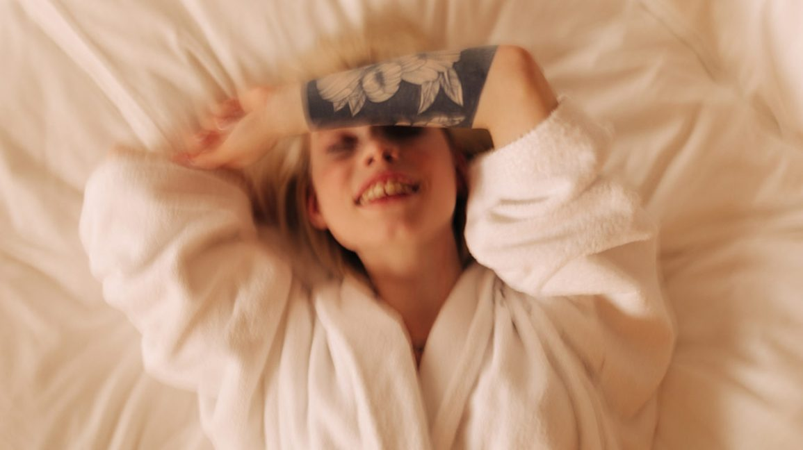 person wearing a bathrobe laying on their back in bed, smiling