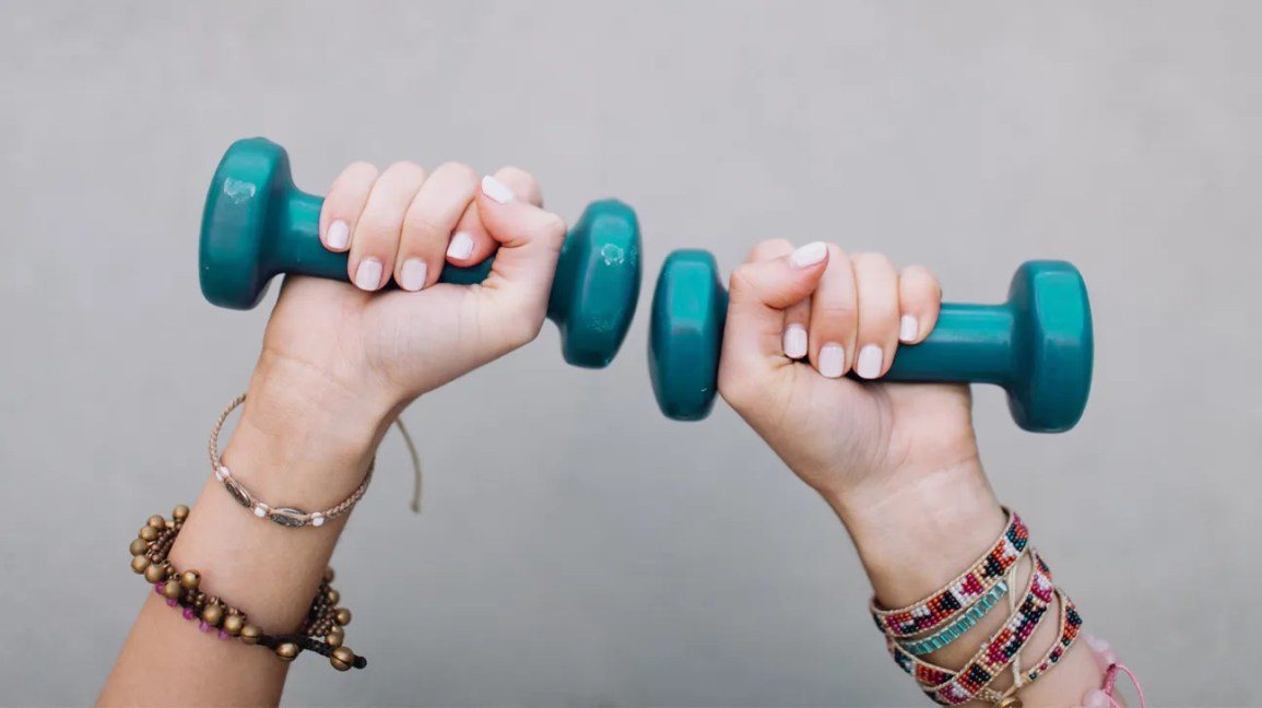 cropped, hands-only view of person with pastel pink fingernails and multicolor beaded bracelets on each wrist holding two 4-pound teal dumbbells overhead