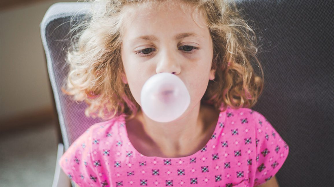A girl making a bubble with bubble gum