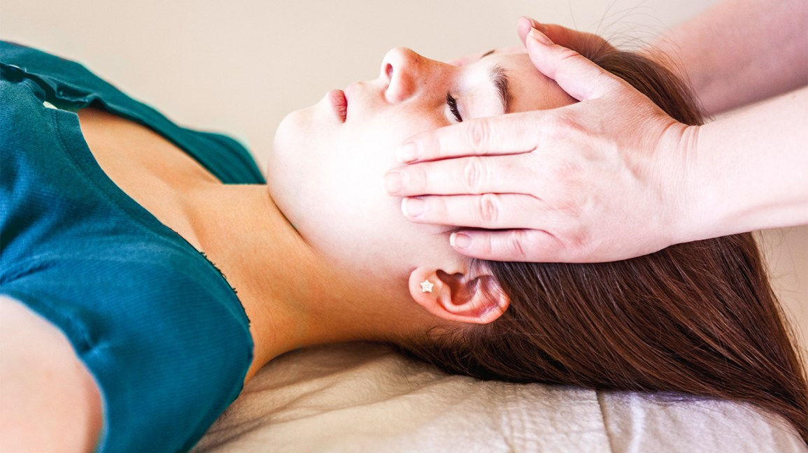 closeup of woman's head on massage table being touched by two hands on either side