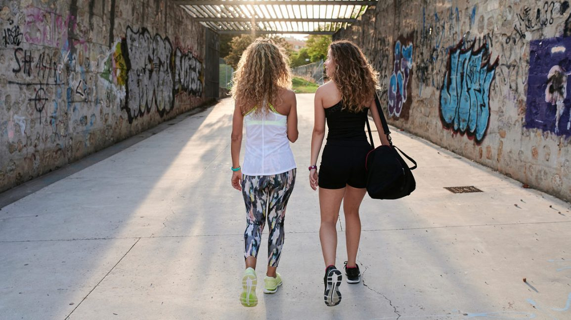 two women walking down a sunlit corridor