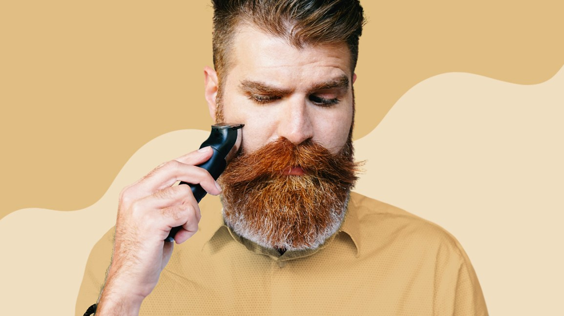 man with a full beard and mustache using an electric shaver