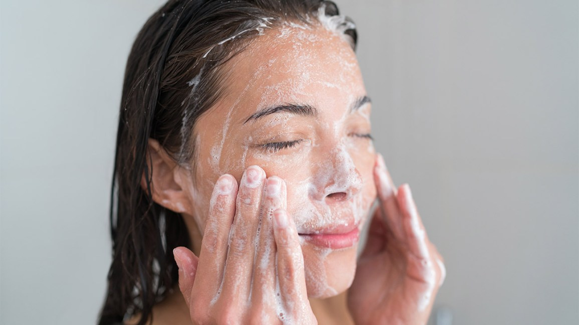 A woman gently exfoliating her skin by massaging a facial scrub on her face with her fingertips.