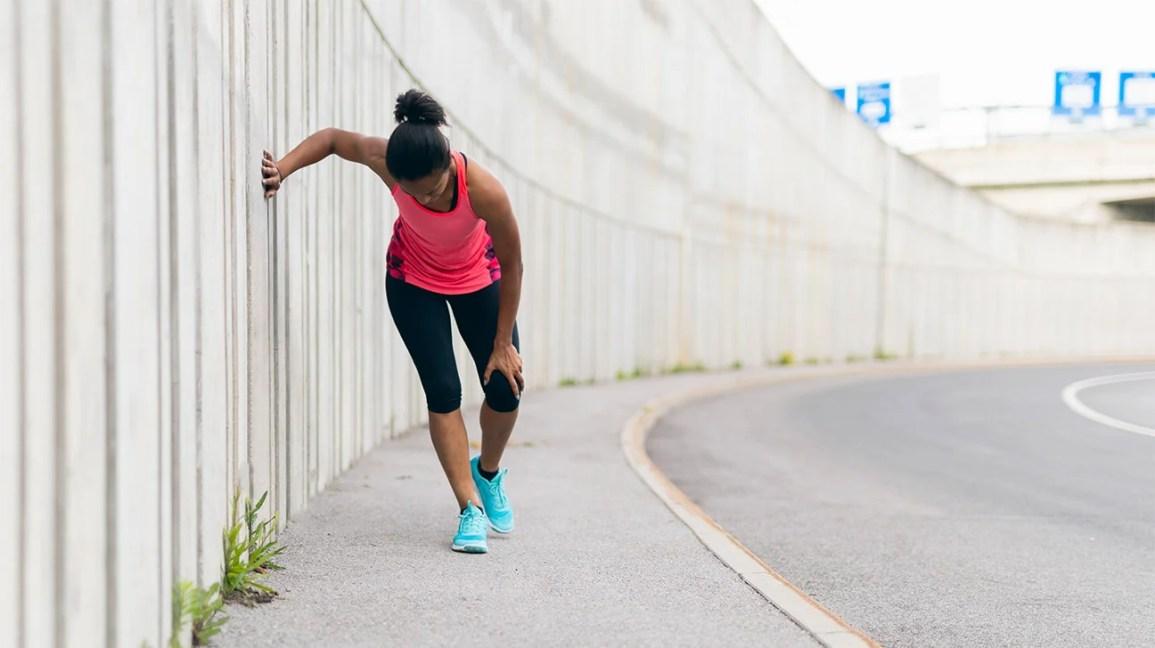 조깅 경로에서 몸을 굽히고 윗다리를 잡고 통증이있는 듯 한 여성.