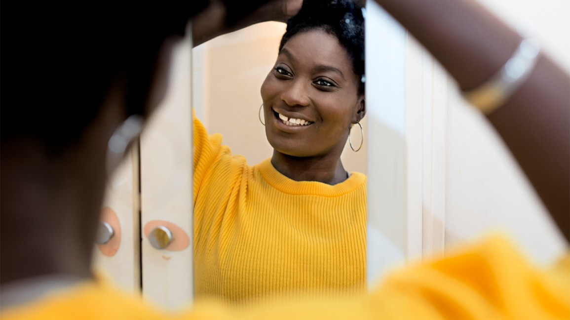 African American woman looking in a mirror