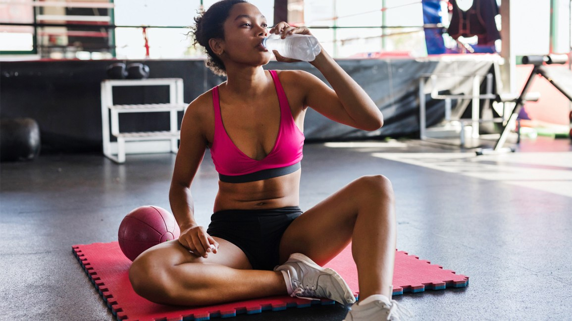African American woman drinking oxygenated water at a gym