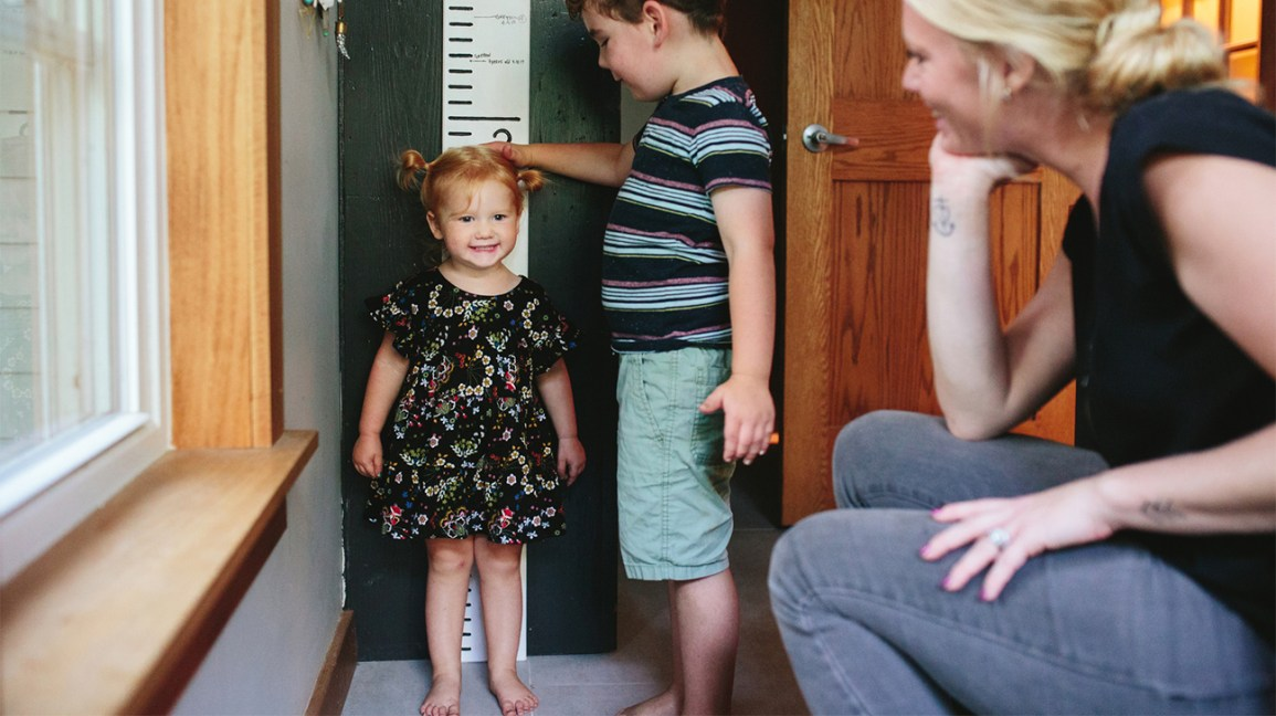 Brother measuring the height of his little sister while their mother watches