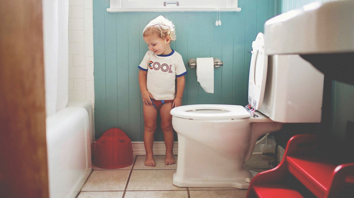 Toddler in bathroom next to toilet