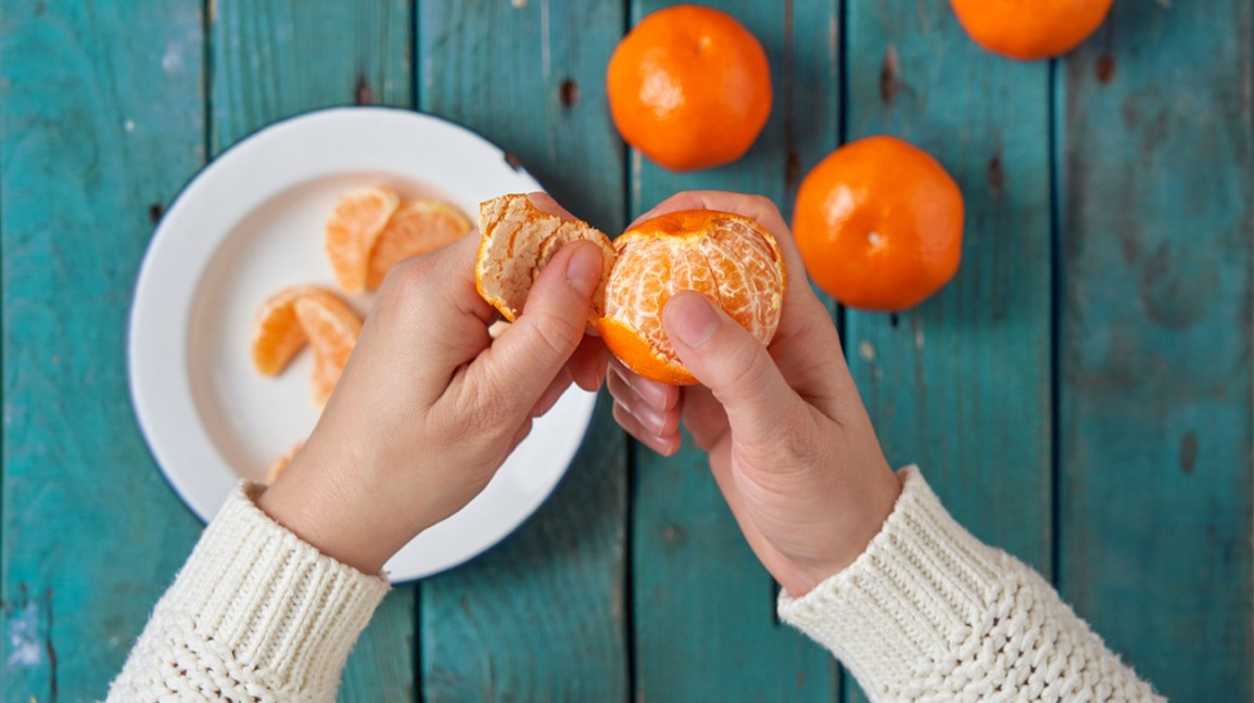 Person peeling a clementine