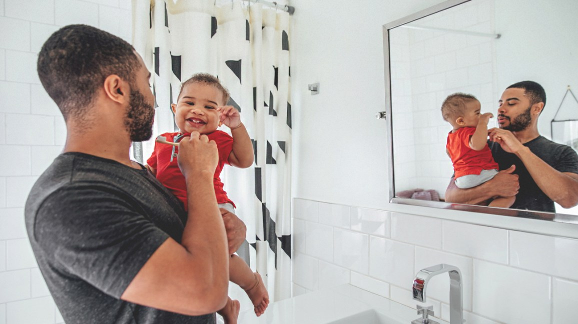man brushing baby's teeth