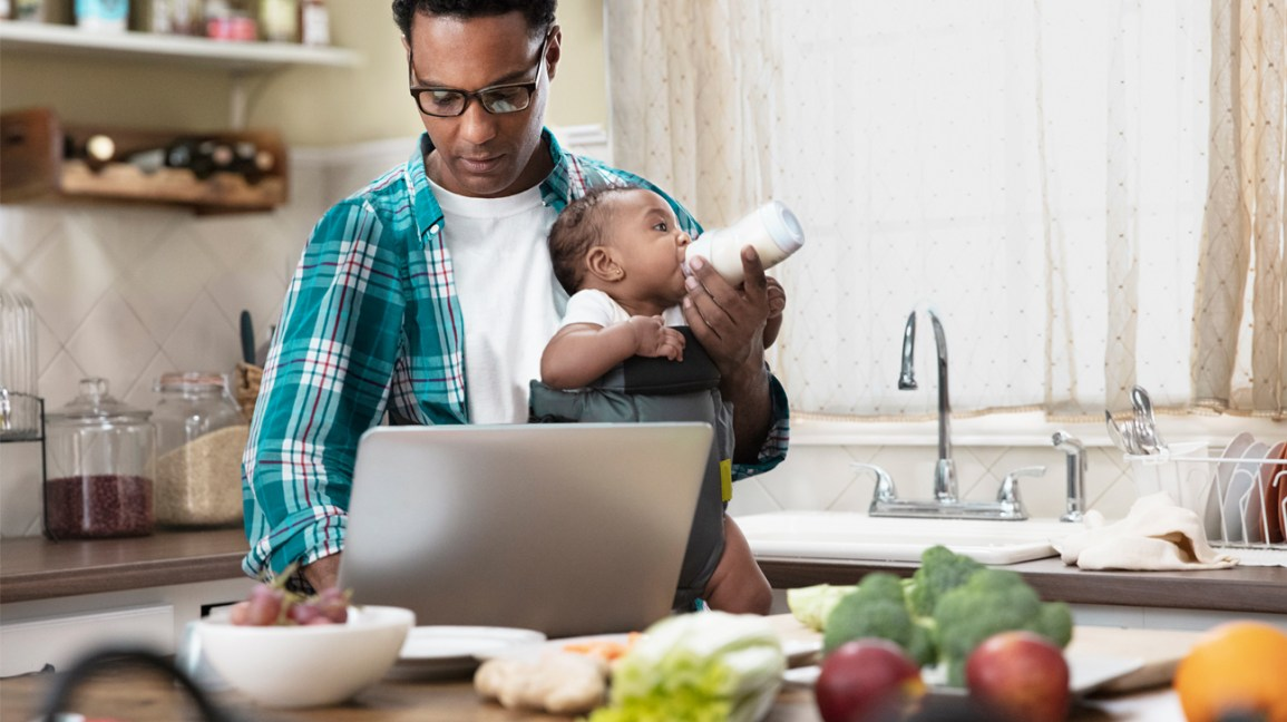 man working in kitchen while feeding baby