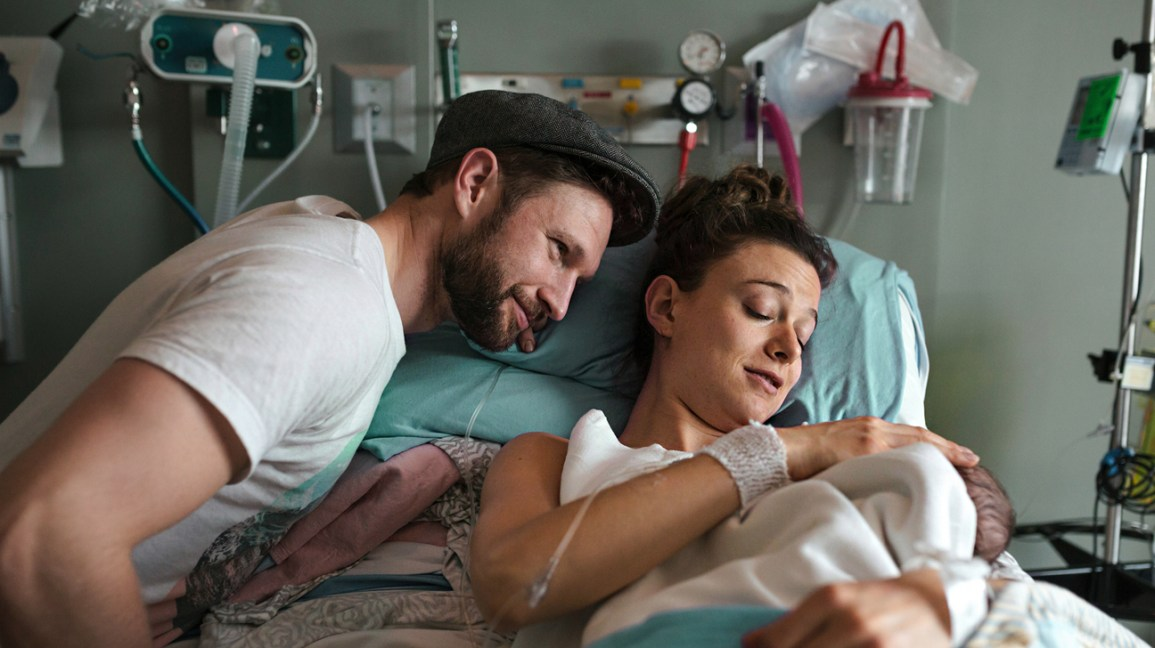 parents cuddle newborn in hospital