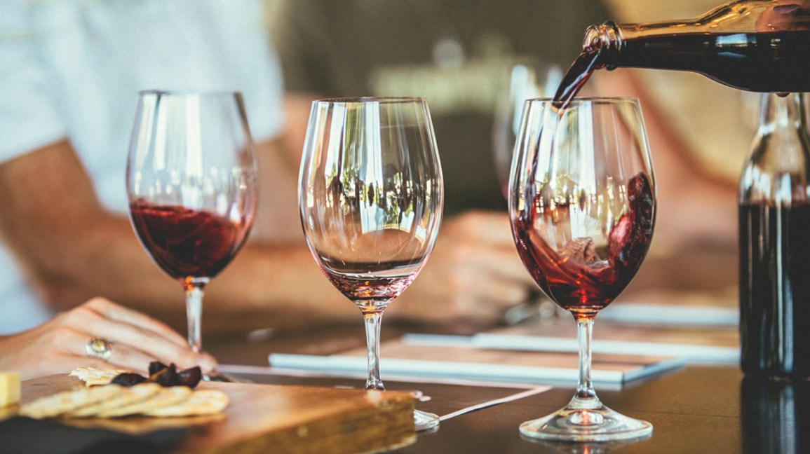 Glasses of wine on a table, which can be a cause of tooth discoloration and teeth staining.