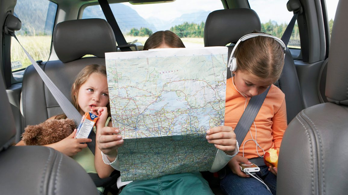 three sisters in the backseat studying a map