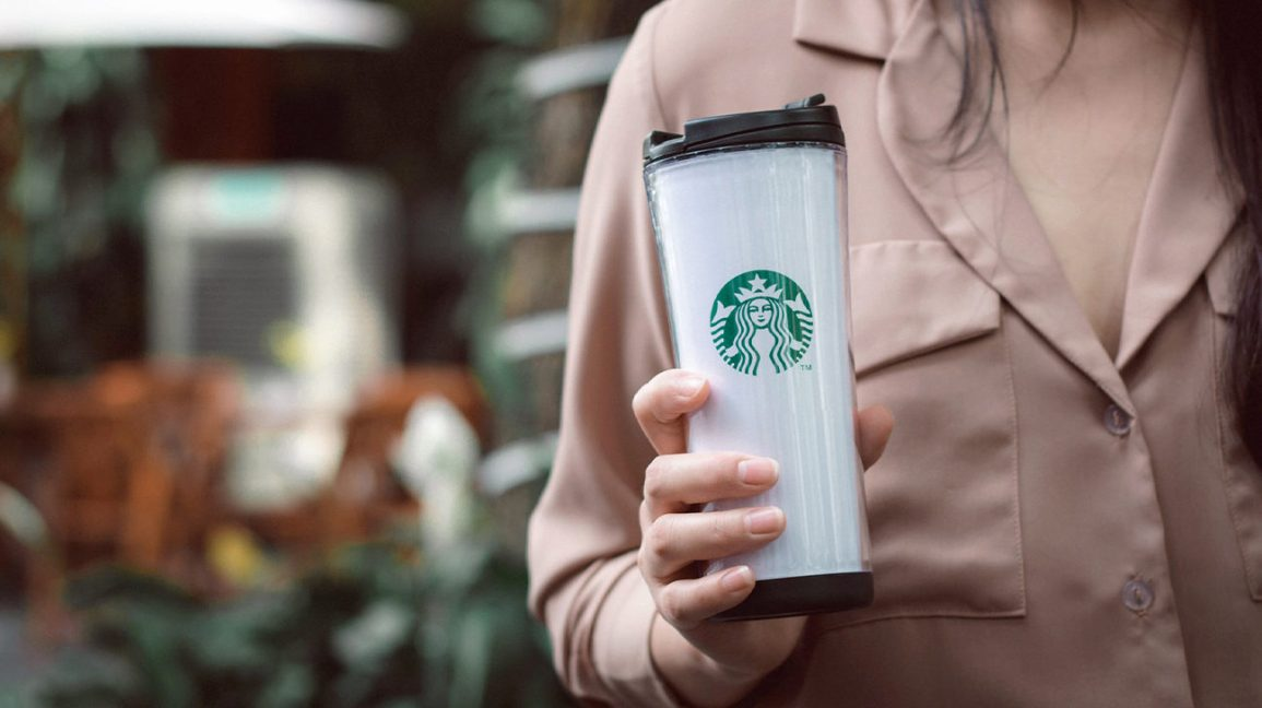 woman holding Starbucks travel mug
